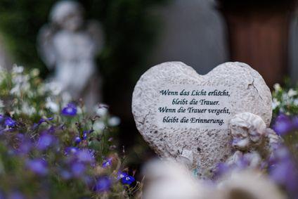 Foto des herzförmigen Gedenksteins im Friedhof, umgeben von Blumen
