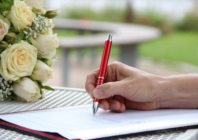 Person gibt Unterschrift auf einem Formular
